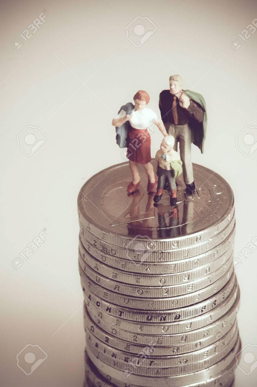 Miniature family on pile of coins. Standard-Bild - 29607786