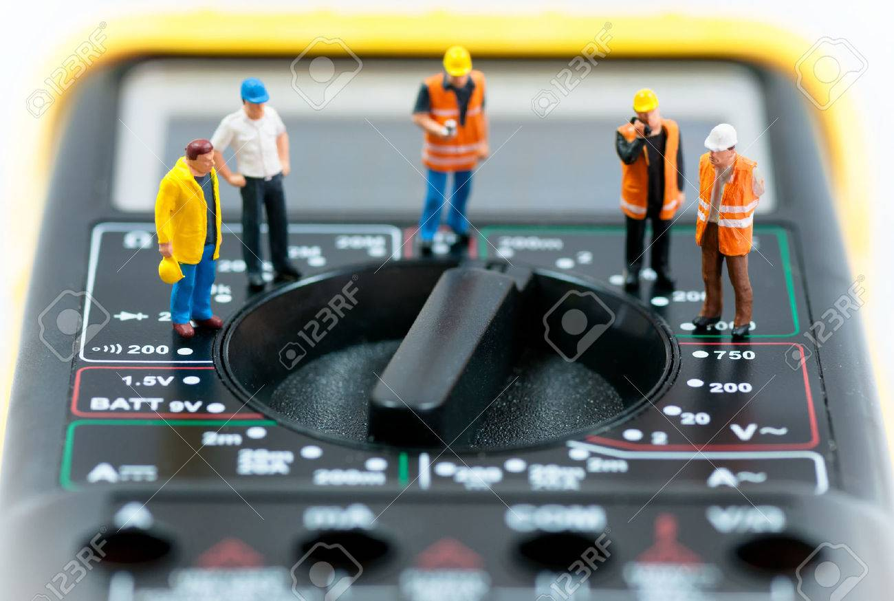 Team of miniature workers on top of multimeter  Macro photo Standard-Bild - 30162288