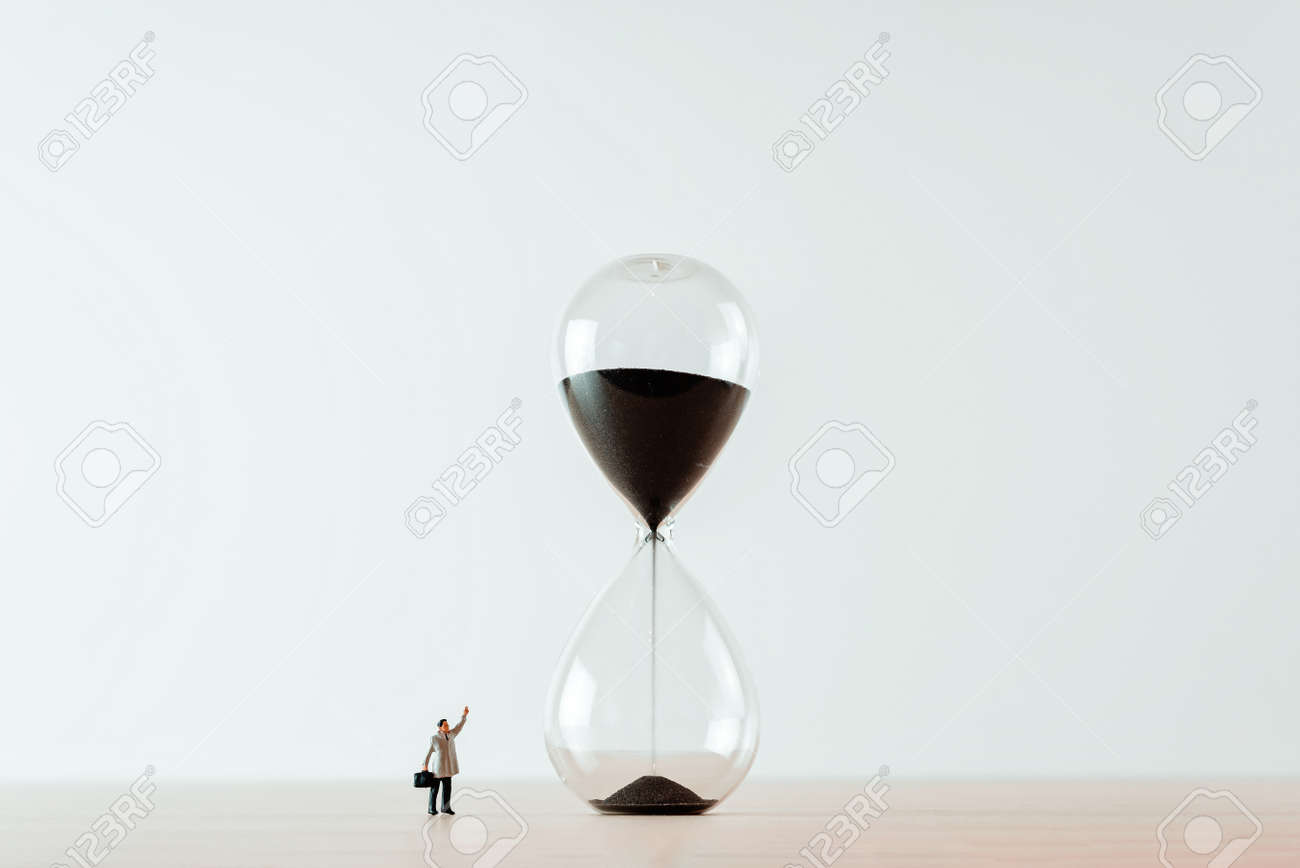 Lonely businessman and giant snad clock. Business concept - 157377030
