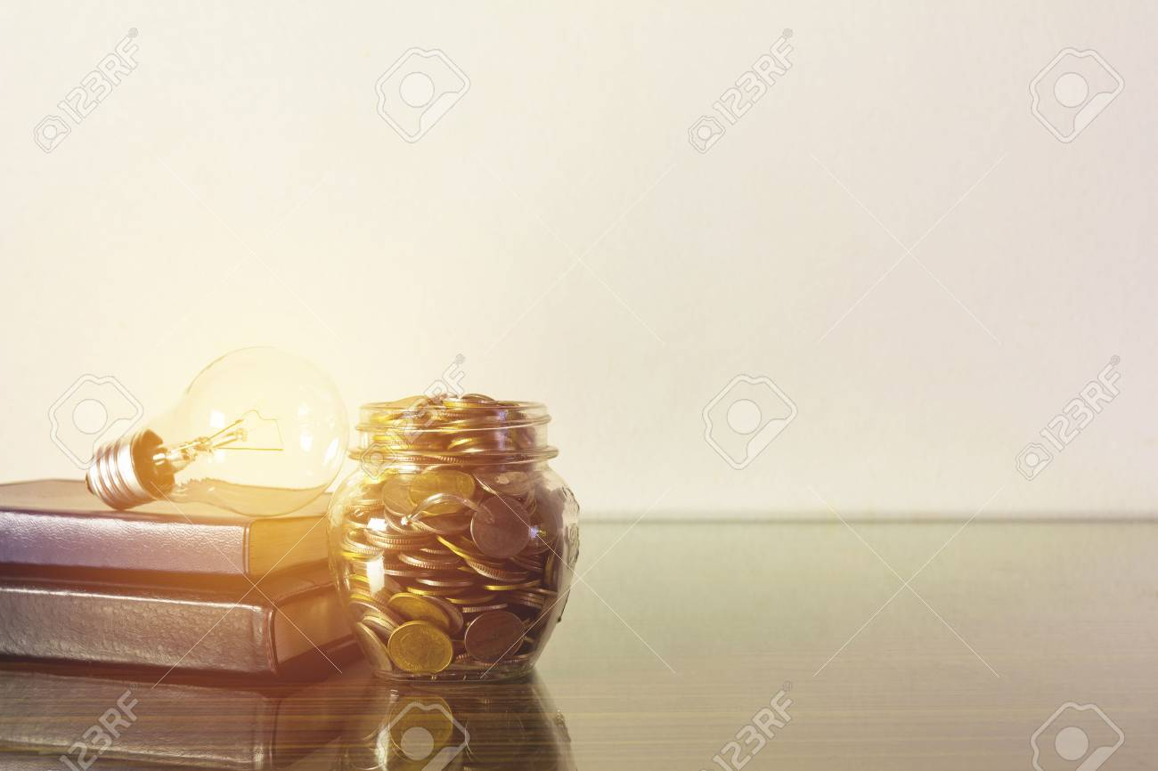 Saving money concept light bulb on books with money in the bottle glass growing for business sepia style. - 87599690
