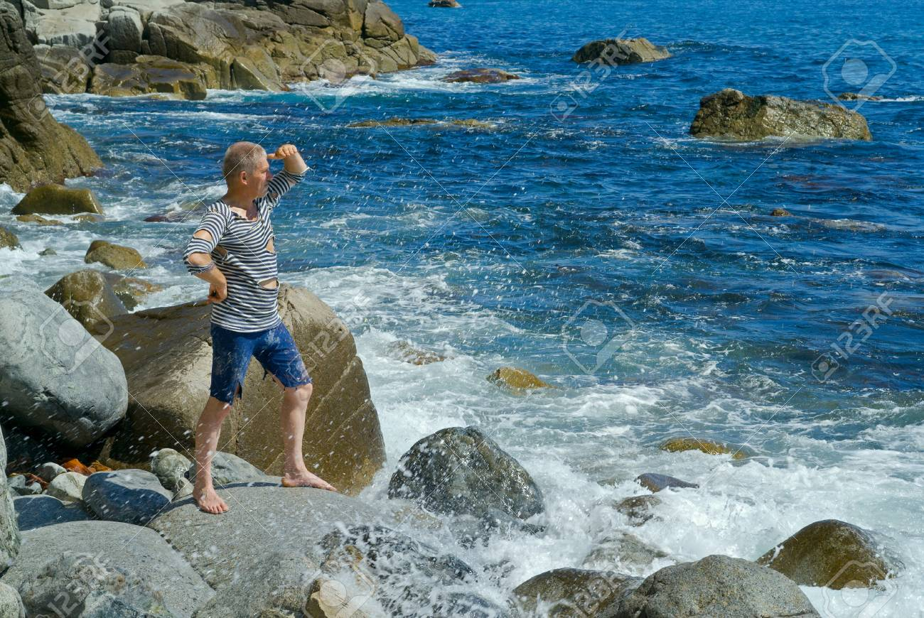 The man in old striped vest on stones at surf. Stock Photo - 10268636