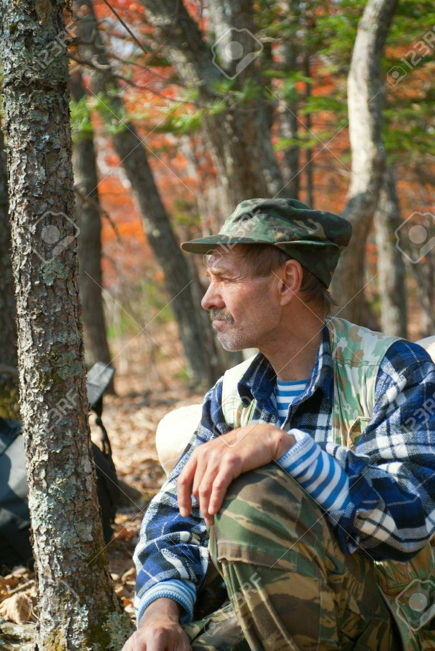 The man sits and relaxes in autumn forest. Stock Photo - 11568233