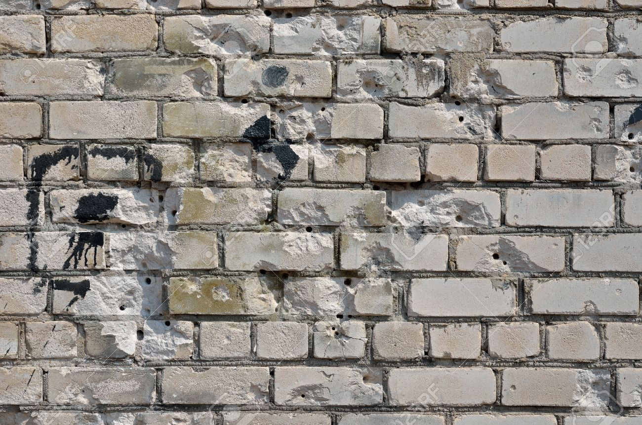 A Close Up Of The Brick Wall With Bullet Holes Stock Photo