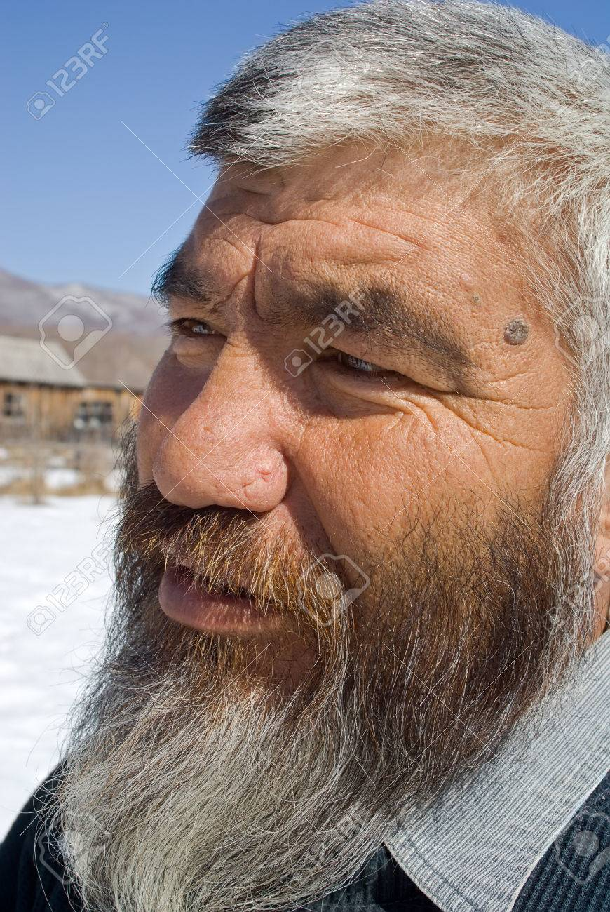 A portrait close up of the old mongoloid man with grey beard