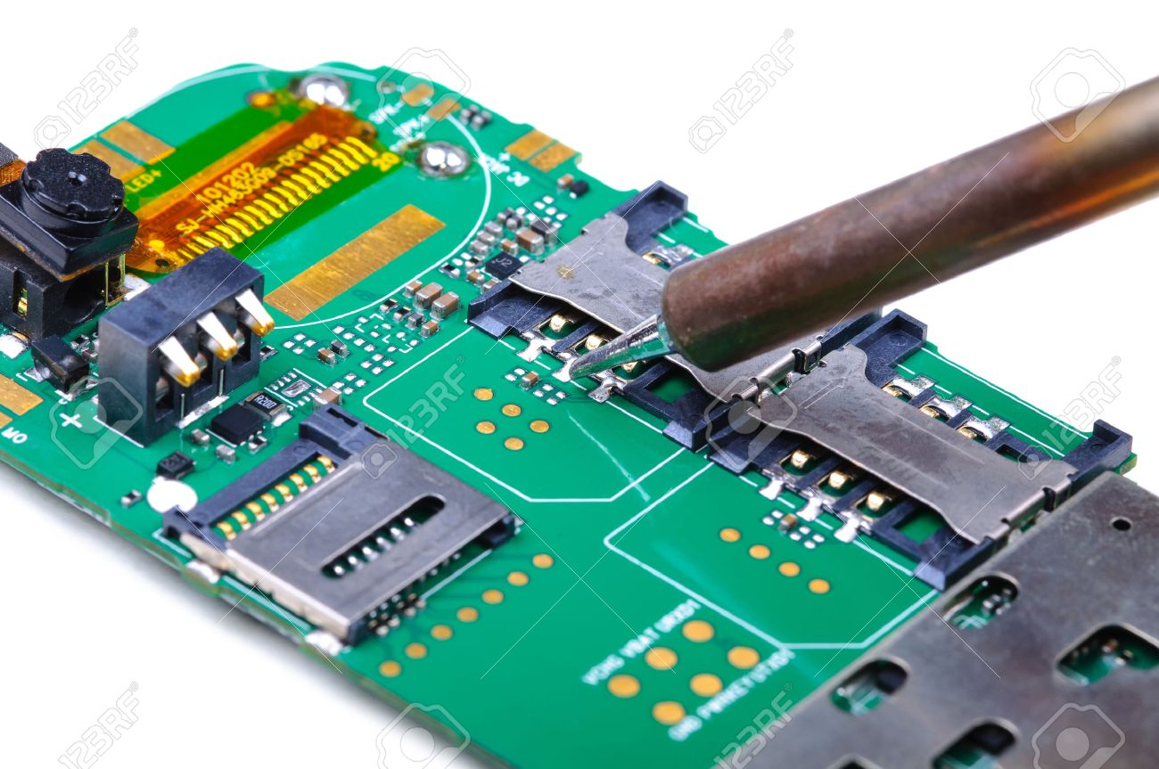 electronic technician repairs sim slot on mobile phone circuitelectronic technician repairs sim slot on mobile phone circuit board close up with selective focus