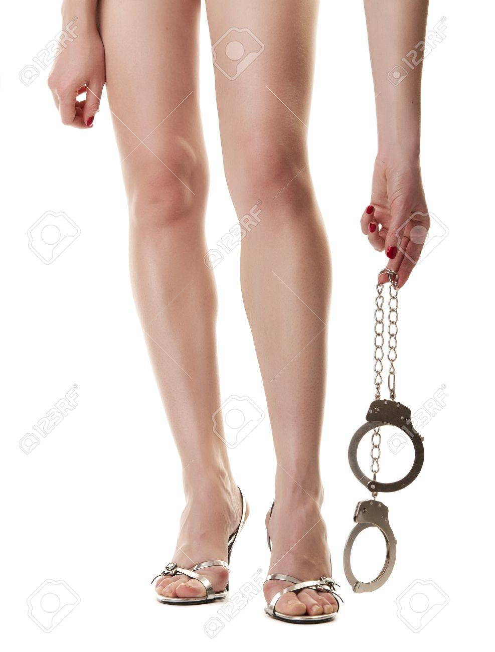 A pair of long female legs and hand holding handcuffs. Isolated on white background Stock Photo - 9507710