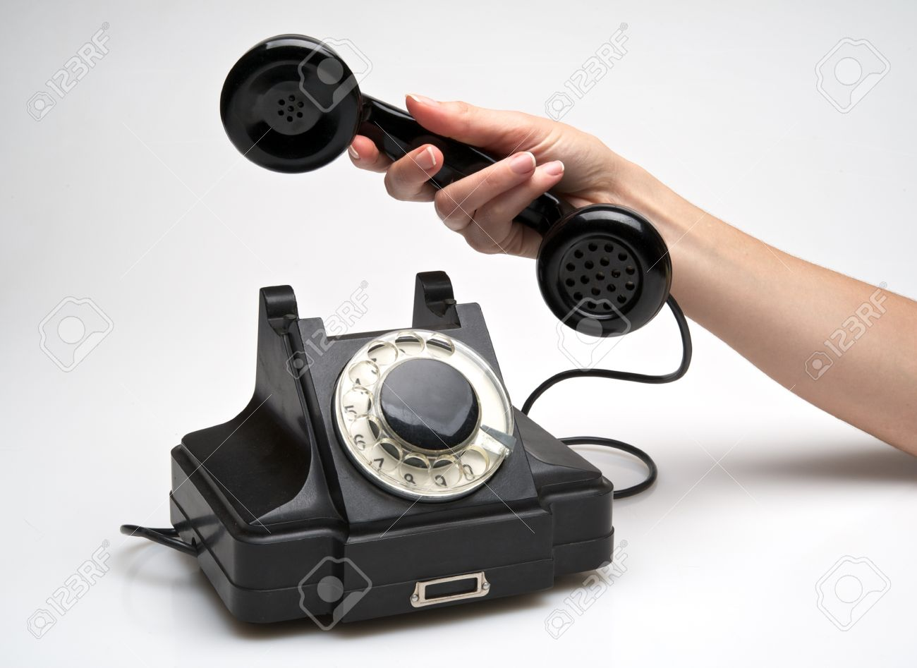 woman hand hanging up the handset of an old black telephone isolated ocer white background Stock Photo - 10126830