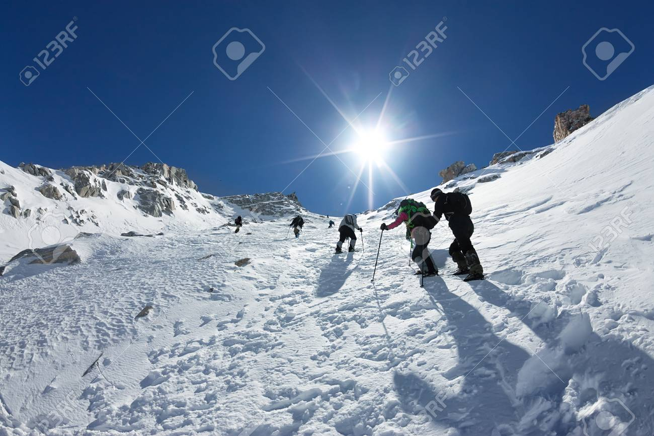 Tied climbers climbing mountain with snow field tied with a rope with ice axes and helmets - 113611495