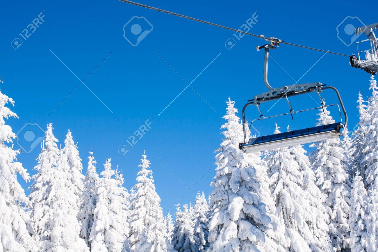 empty chair lift new ski resort image with empty chair lift blue sky and white snowy pine trees at resort image with empty chair lift blue sky and white snowy