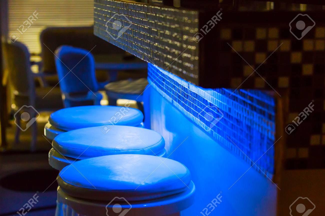 Sgabelli da bar vuoti lungo bar illuminato in azzurro viola foto