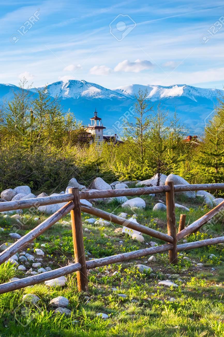 Paysage Avec La Cloture En Bois Les Arbres De Printemps La Tour De Bois Du Chalet Et Les Sommets Enneiges Des Montagnes A Bansko En Bulgarie