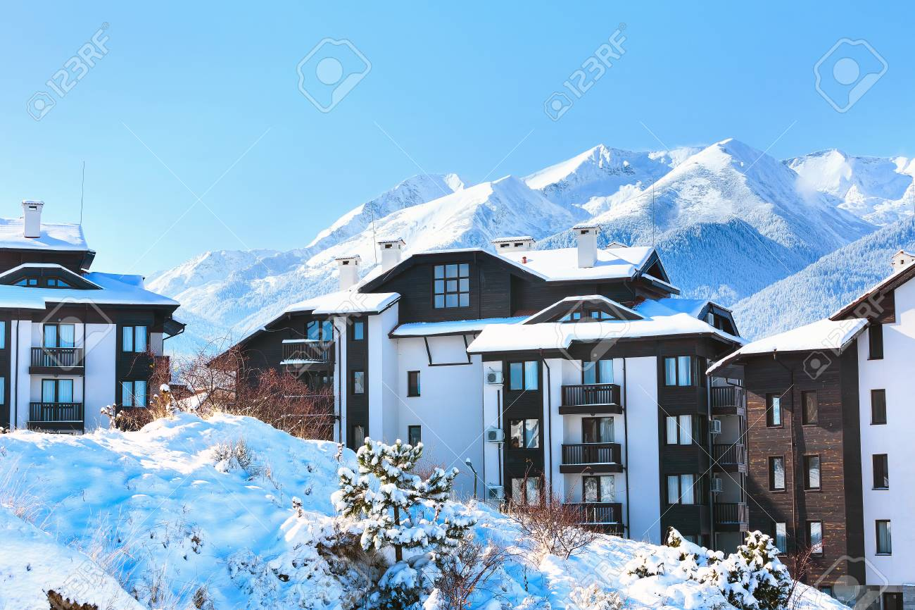 wooden chalet, houses and snow mountains landscape panorama in