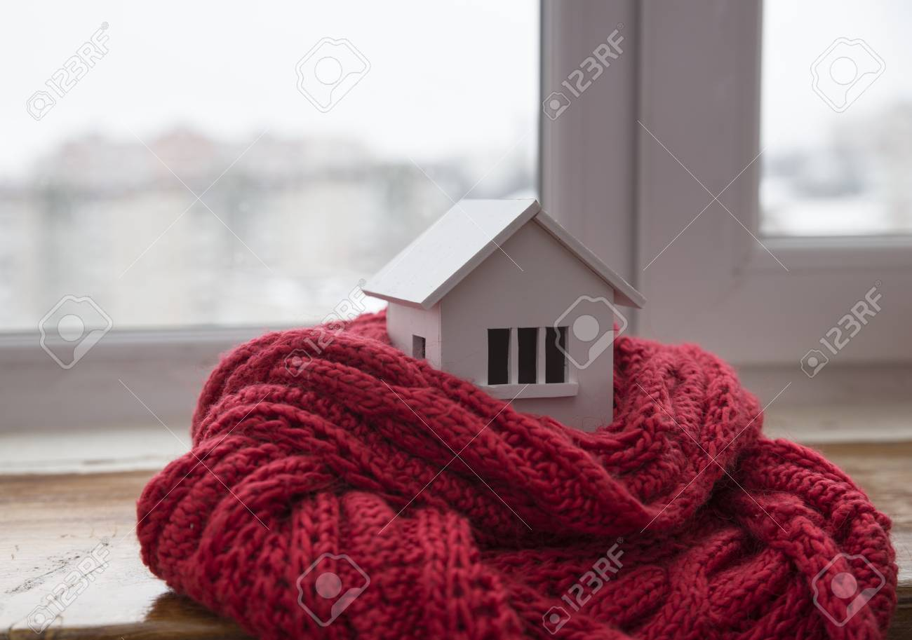 house in winter - heating system concept and cold snowy weather with model of a house wearing a knitted cap - 91827081