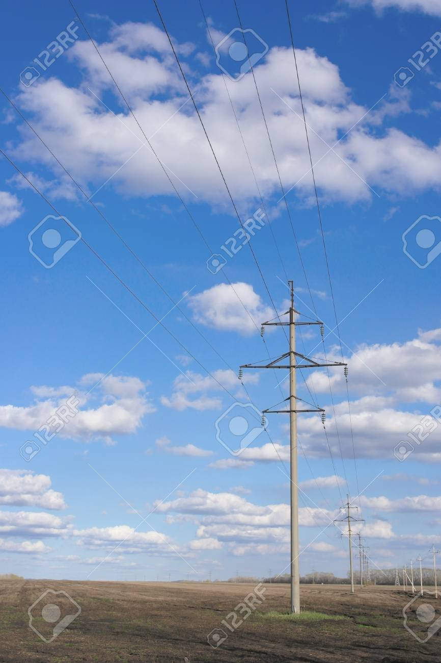 Power line of electricity transmissions on the field - 23769845
