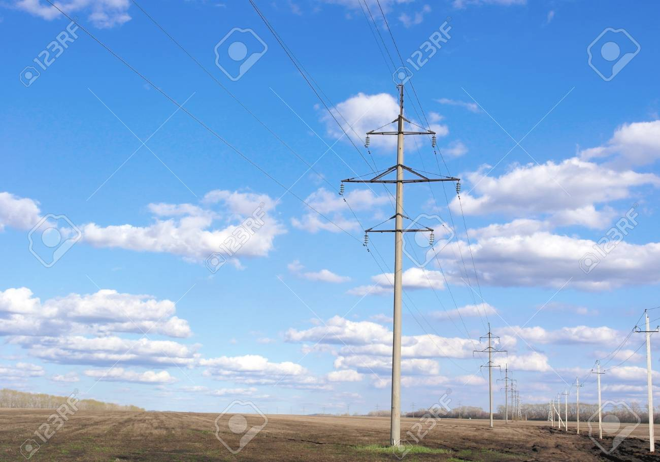 Power line of electricity transmissions on the field - 23769846