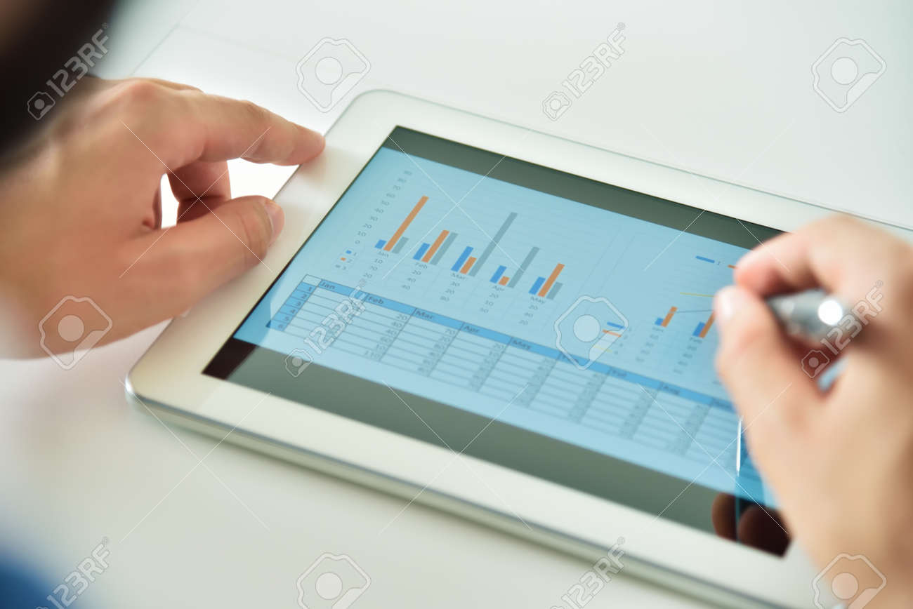 Top view of hand using digital tablet computer with financial data. Business and management concept. Close up - 157402198