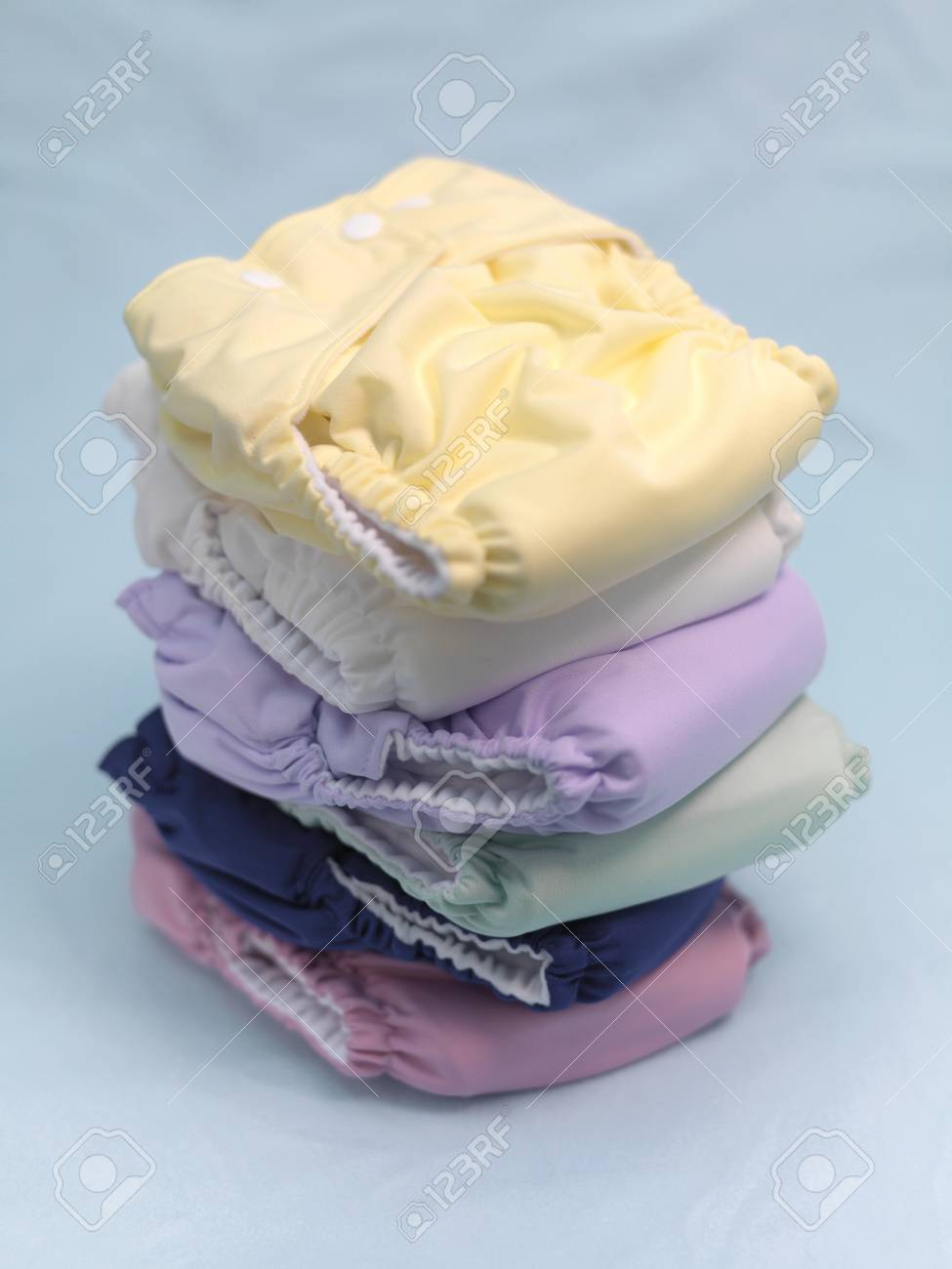A stack of modern cloth nappies isolated against a blue background Stock Photo - 7513614