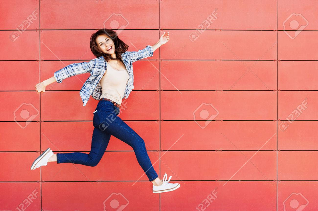 Joyful happy young woman jumping against red wall - 65729523