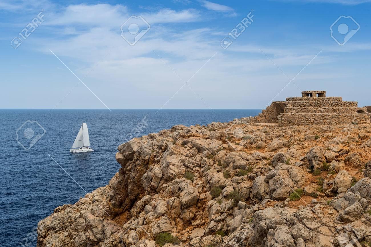 La Maison Au Dessus Des Voiles bateau à voile en face d'une falaise rocheuse avec une vieille maison en  pierre de la ferme minorquine ci-dessus
