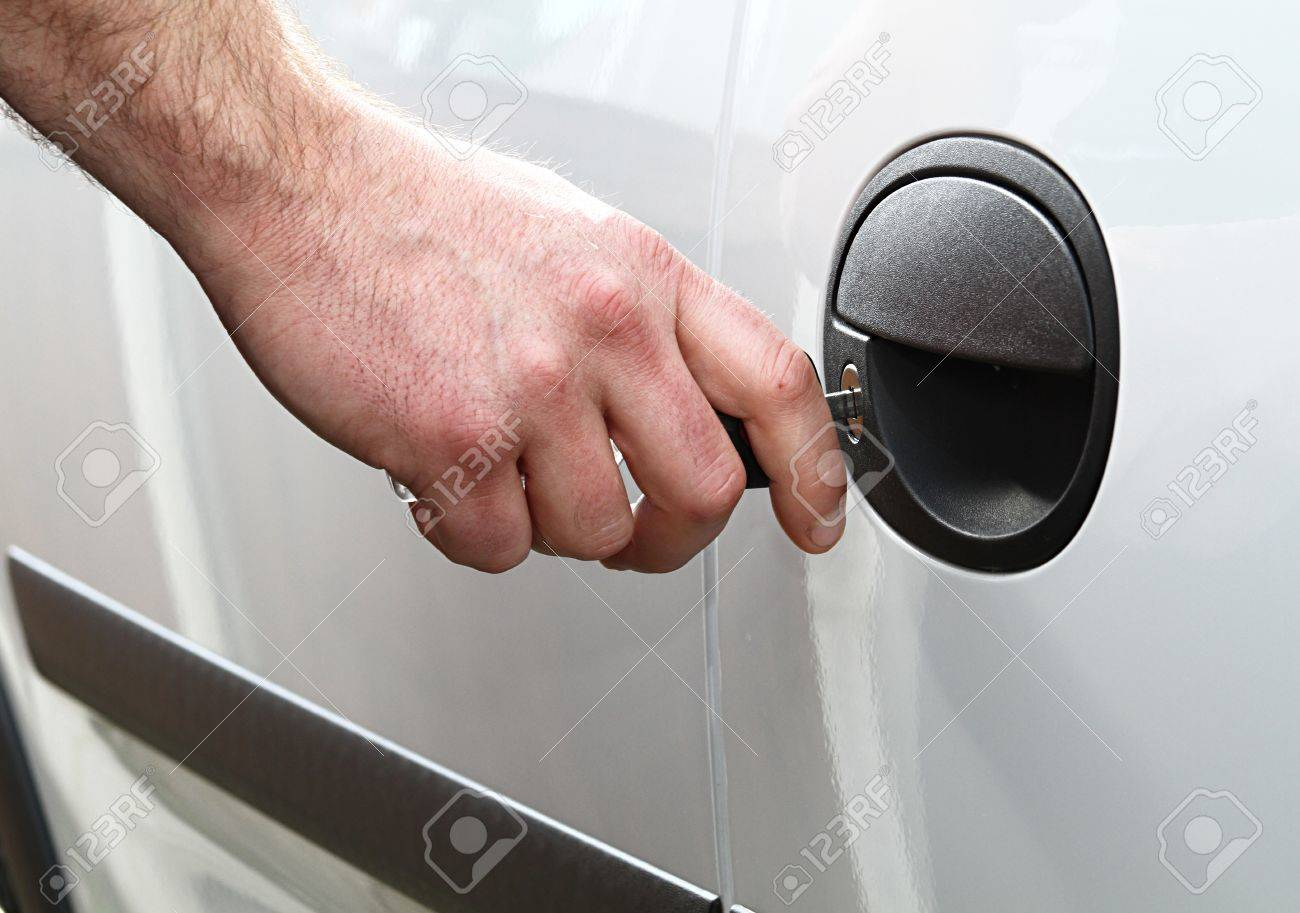 a man locks his car door with his key shot in daylight. Stock Photo - 10522472