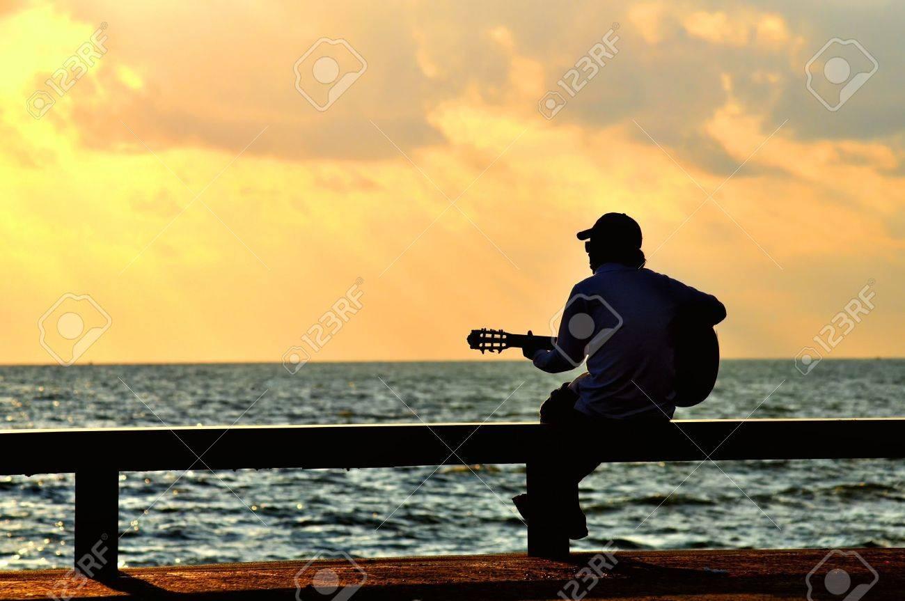 man with guitar at sunset - 17065230
