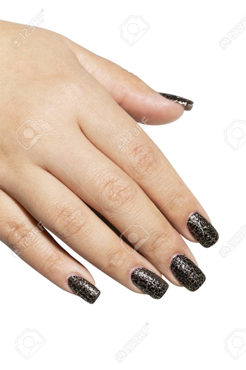 Main avec des paillettes d\u0027or noir et vernis à ongles