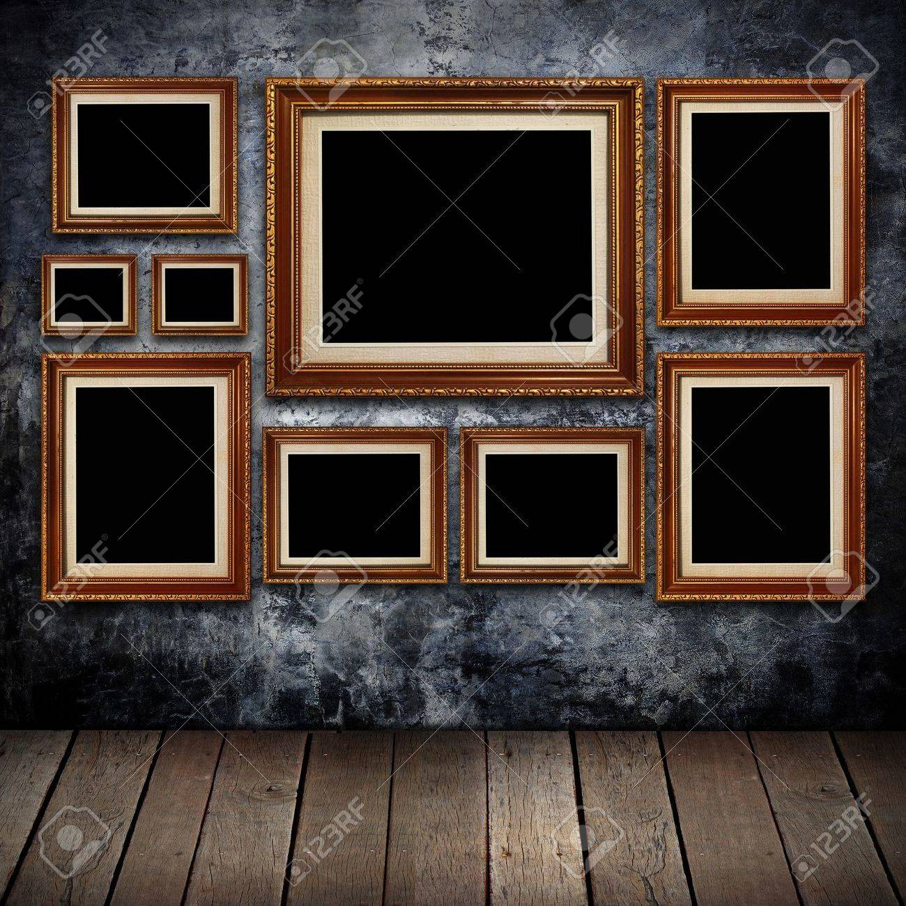 grungy wall with gold frames and old wood background stock photo 12455480