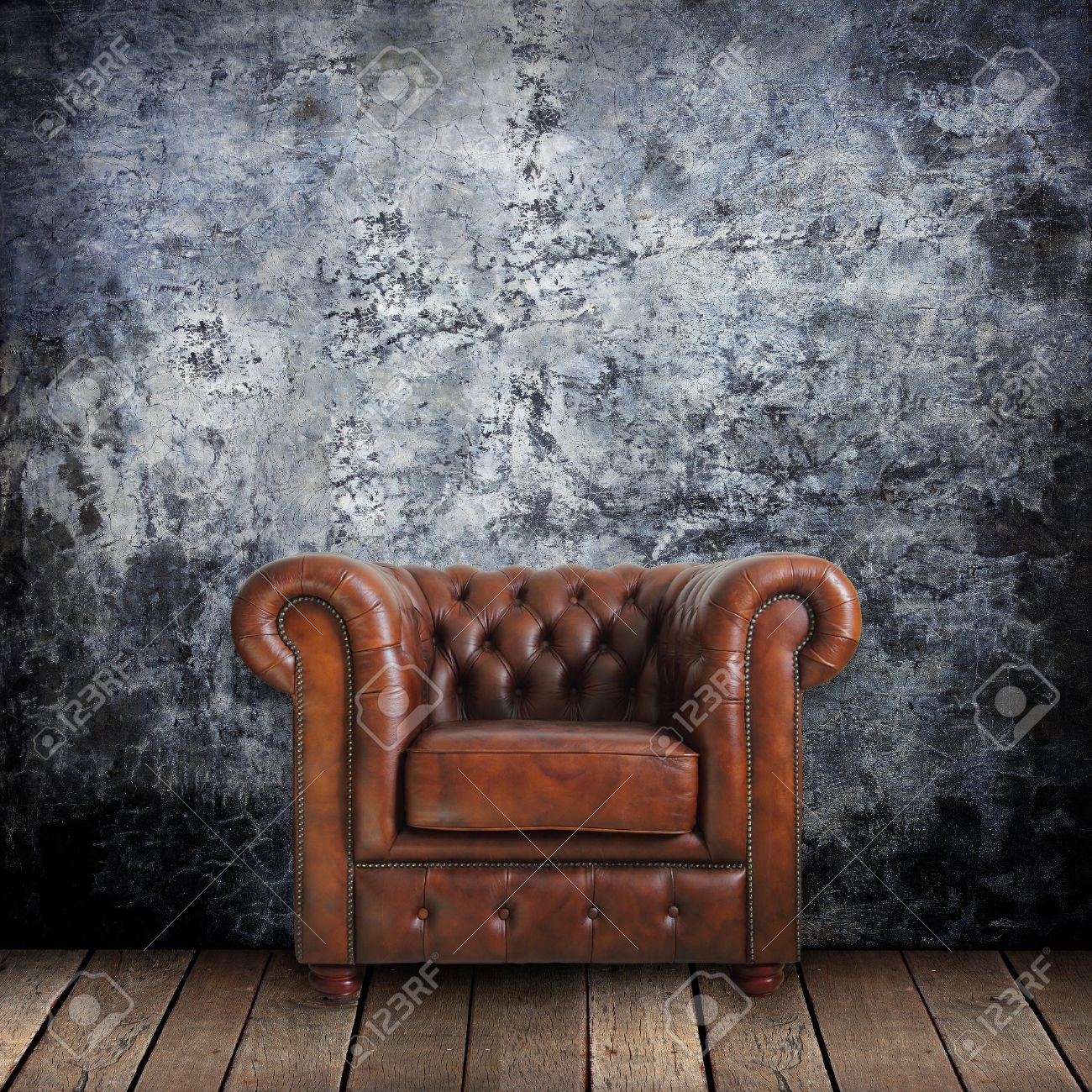 48fbf6d188e Grungy wall with Classic Brown leather armchair and old wood background.  Stock Photo - 12801410