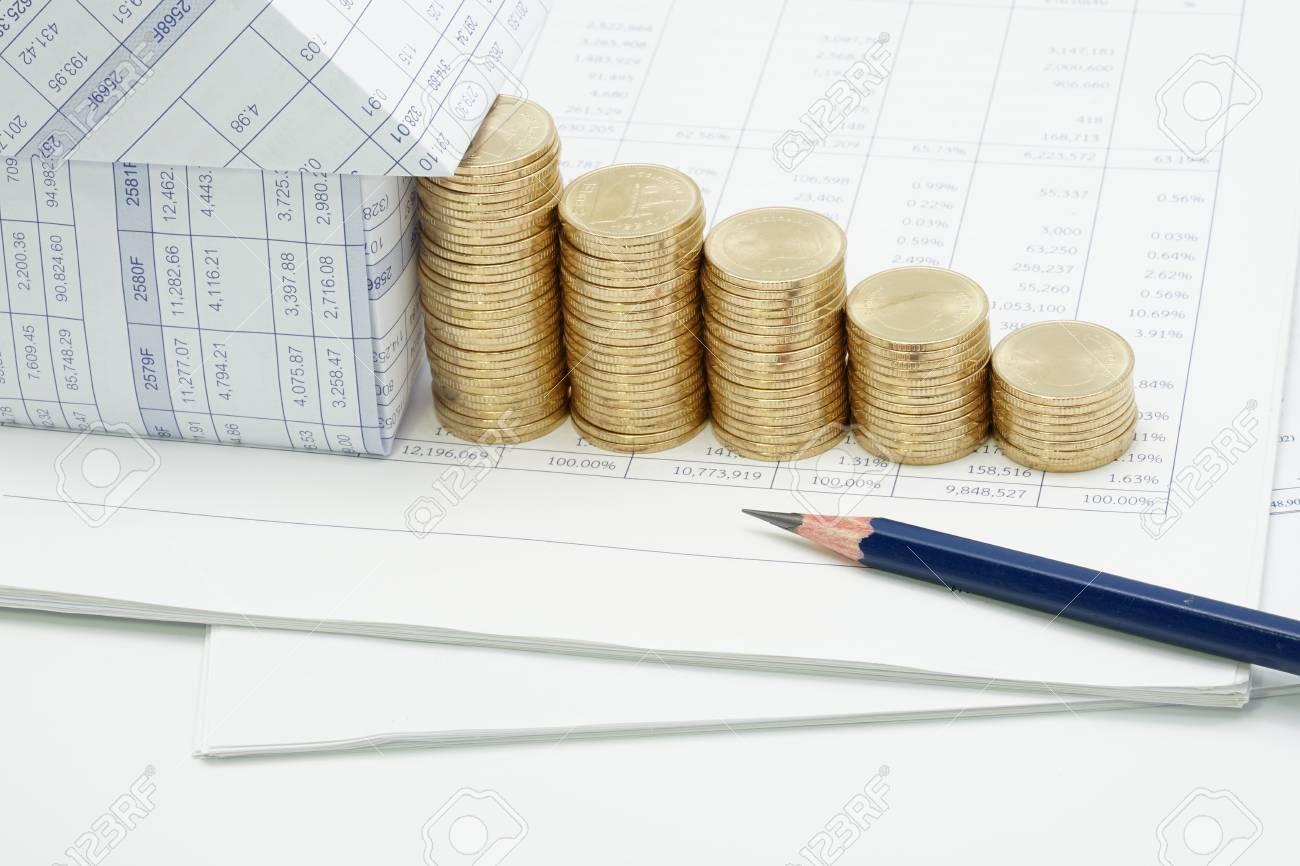 crayon et maison avec empilement de pièces d'or sur compte de