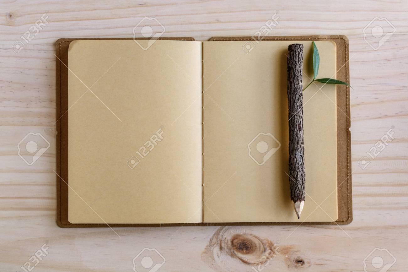 Recyclez le cahier avec un crayon en bois sur le bureau en bois