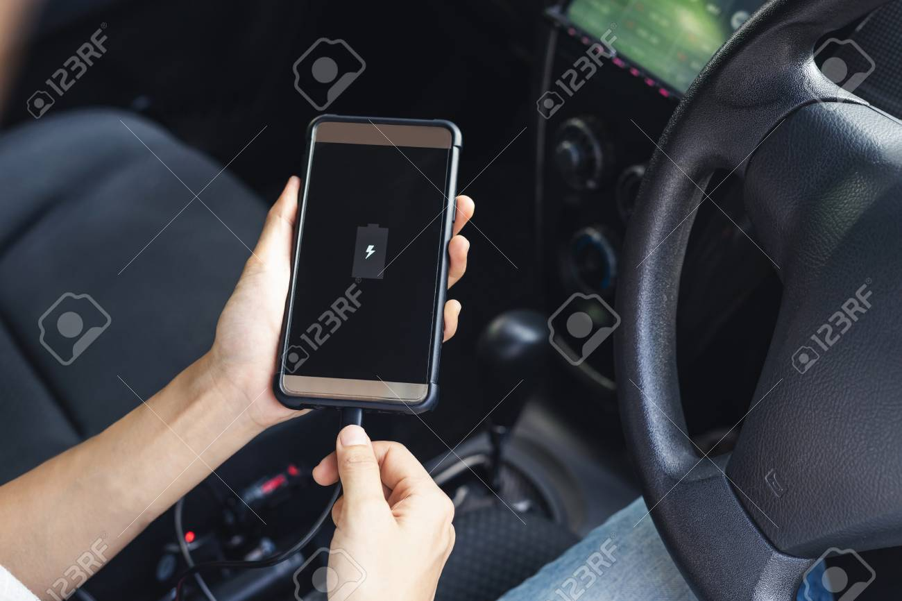 Hand holding smartphone and changing phone battery in car - 103008910