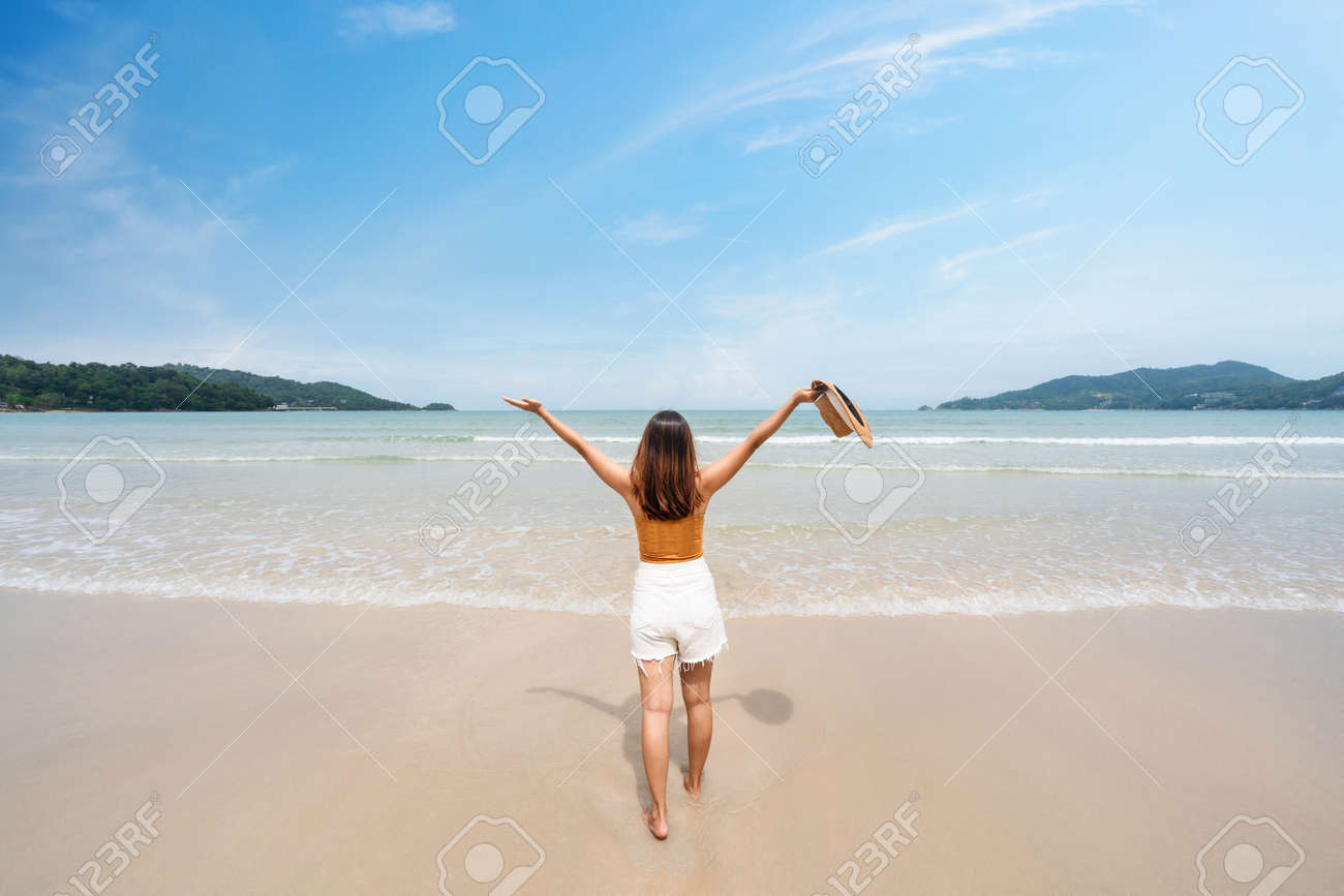Young woman traveler relaxing and enjoying at beautiful tropical white sand beach with wave foam and transparent sea, Summer vacation and Travel concept - 167304537