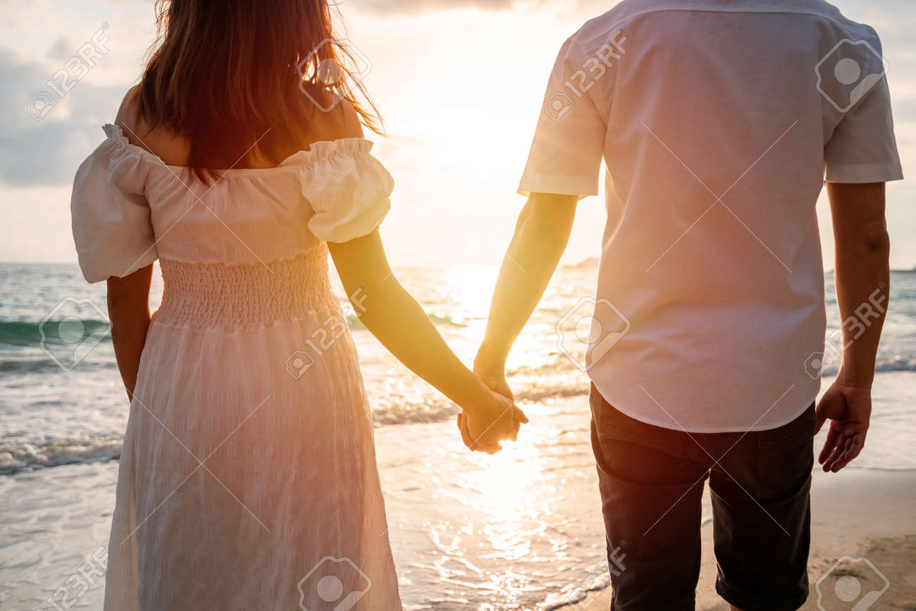 Young woman traveler holding man's hand and looking beautiful sunset on the beach, Couple on vacation in summer concept - 167385260