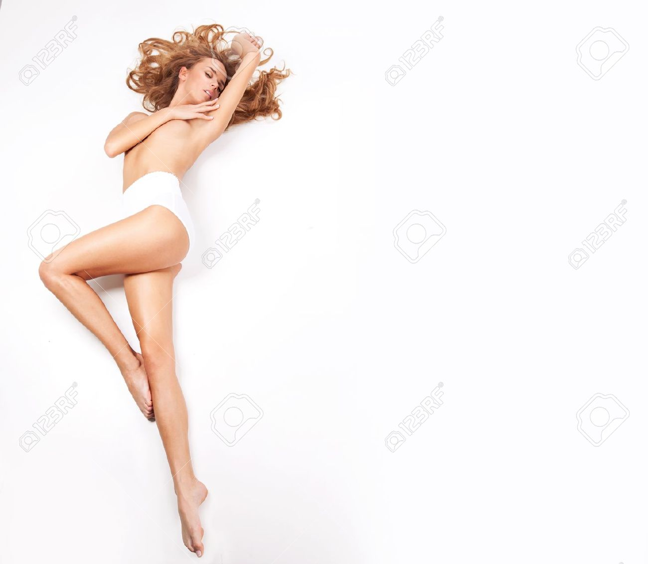 Delicate blond woman lying on a white background Stock Photo - 19398656