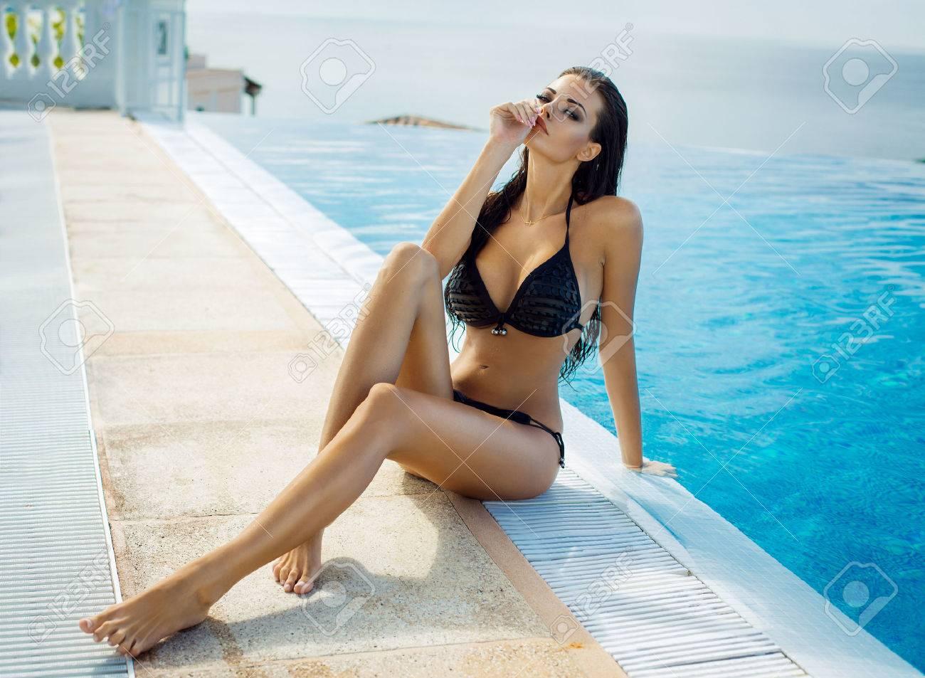 6c4b788560ce Belle femme portant un bikini noir au bord de la piscine dans un paysage  d'été