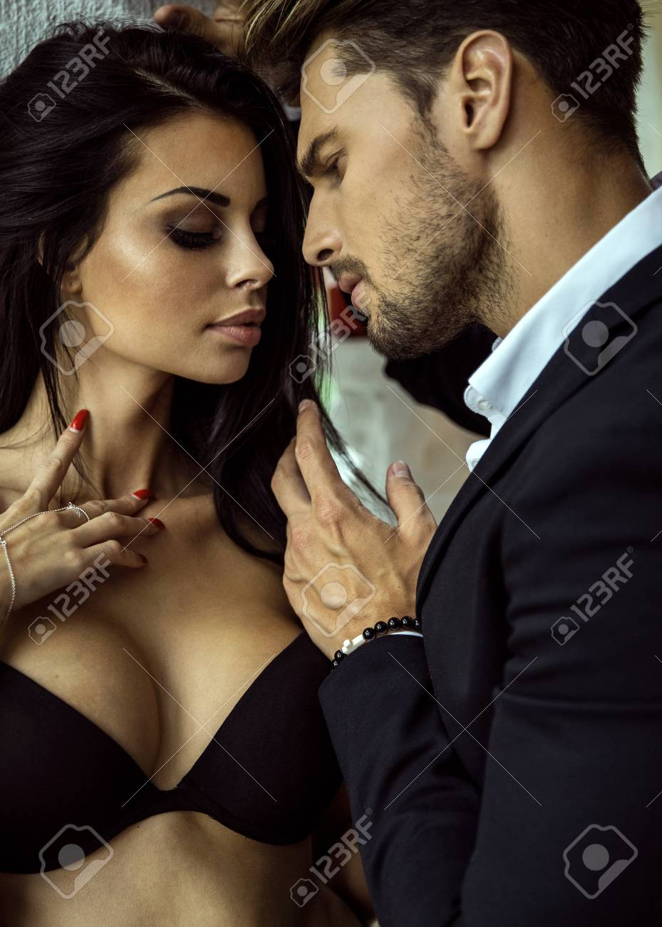 Portrait of sexy man in black suit touching sexy woman in lingerie Stock  Photo - 62176343
