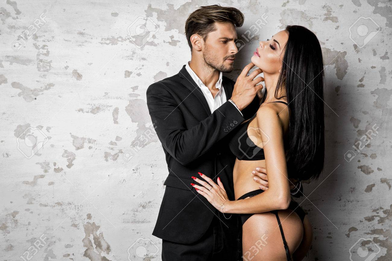 Handsome Man In Black Suit Touching Sexy Woman In Lingerie Stock