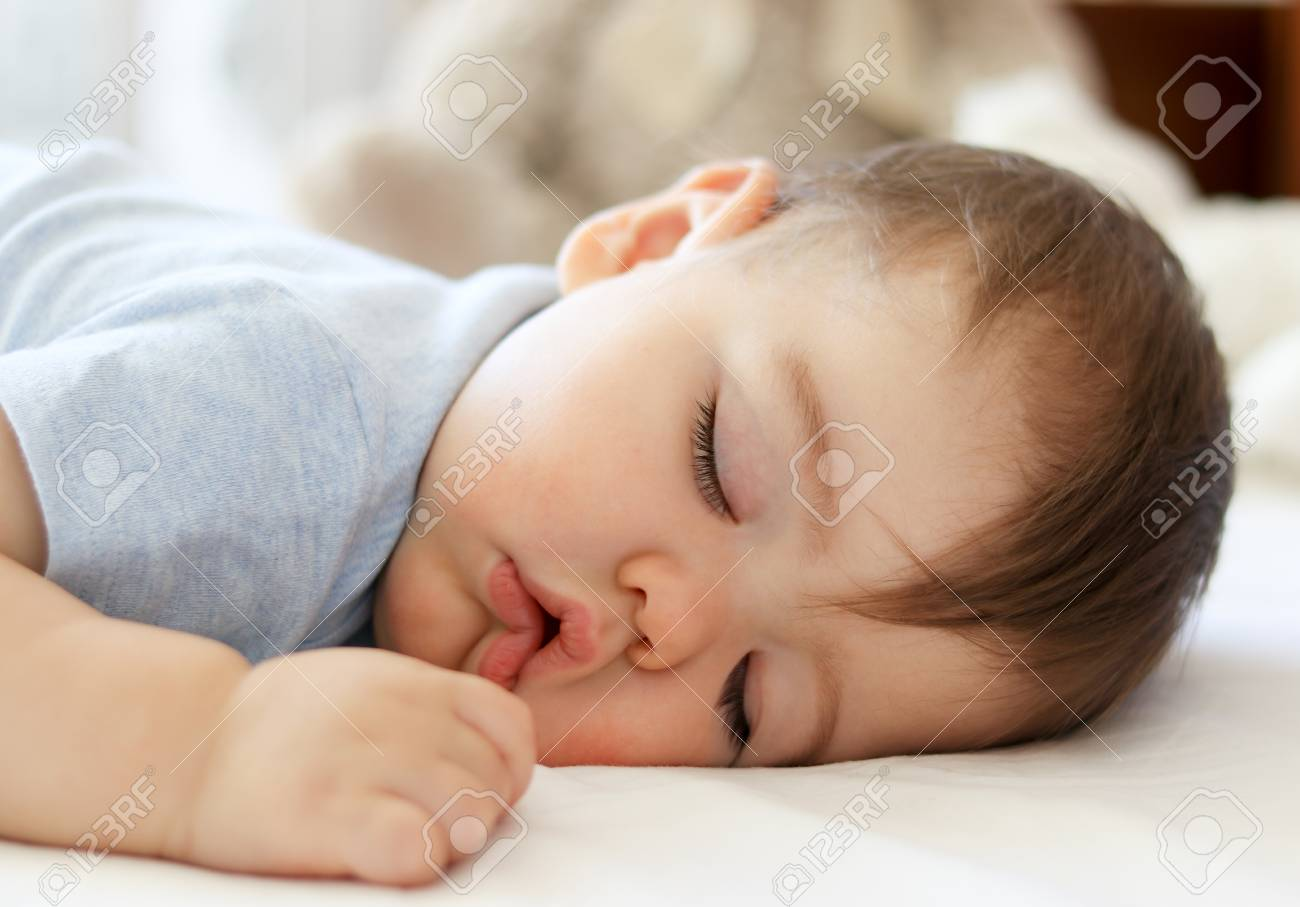 Cute little baby sleeping on stomach with funny open mouth. Daytime sleeping. Close-
