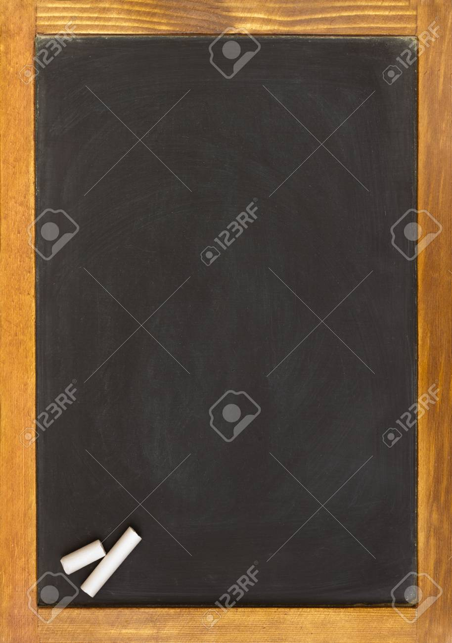 blank slightly dirty chalkboard with an old pine frame two pieces of chalk in one corner