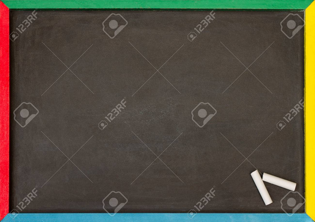 blank chalkboard with multi coloured frame with two pieces of chalk in the corner stock photo