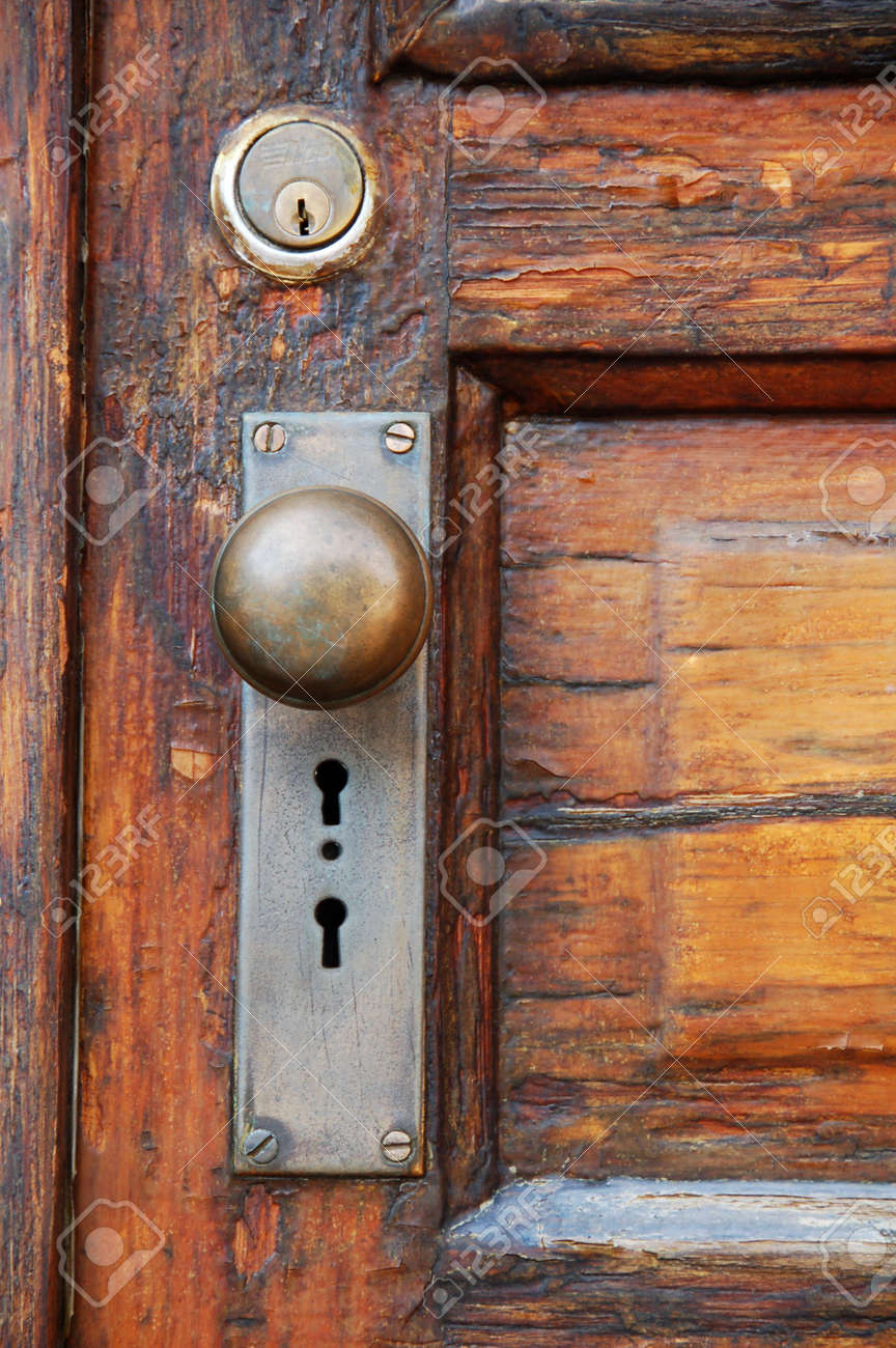 antique door knob on old wooden door with panels stock photo