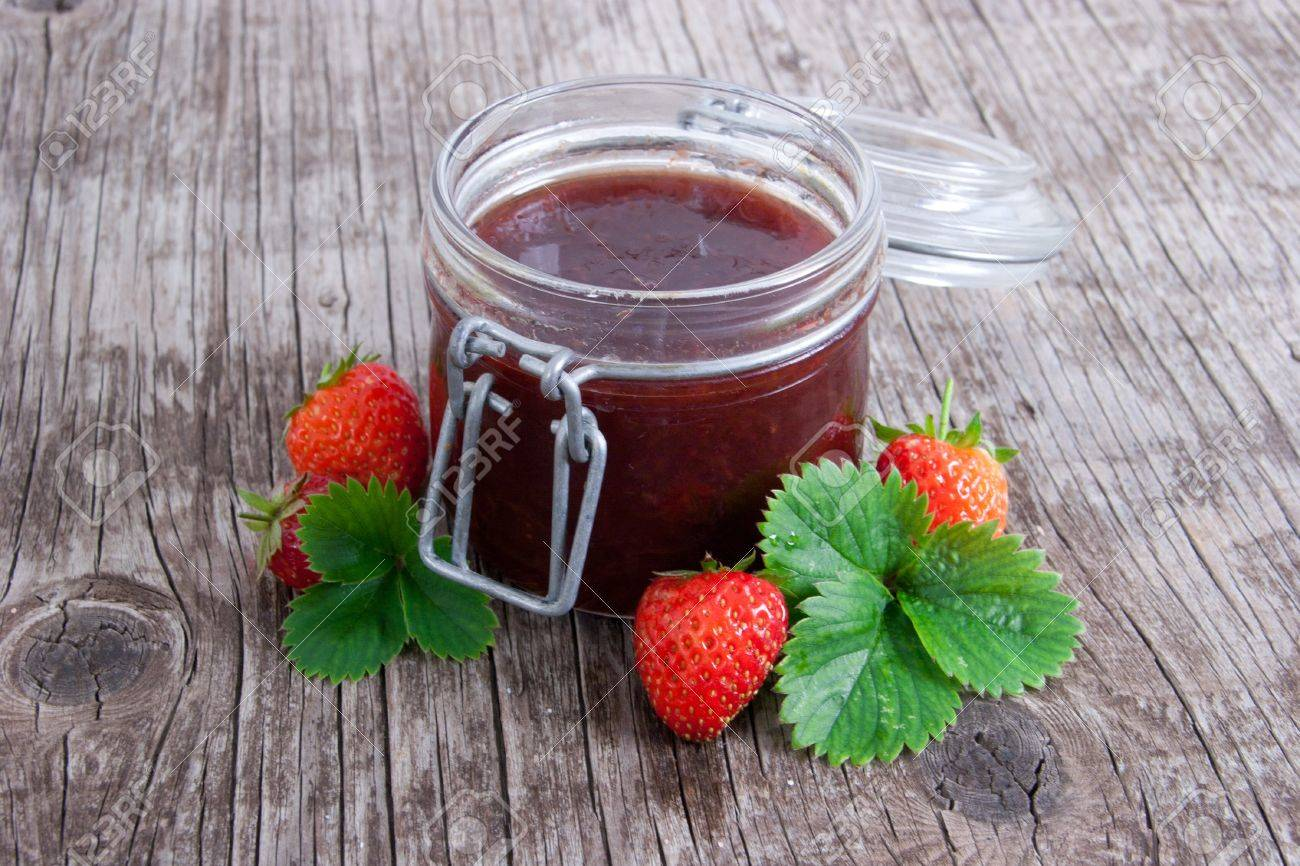 Jar of strawberry jam on rustic wood background with leaves and fruits Stock Photo - 18953669
