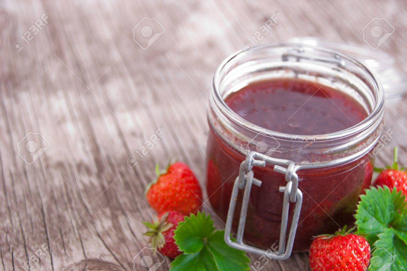 Jar of strawberry jam on rustic wood background with leaves and fruits Stock Photo - 18953609