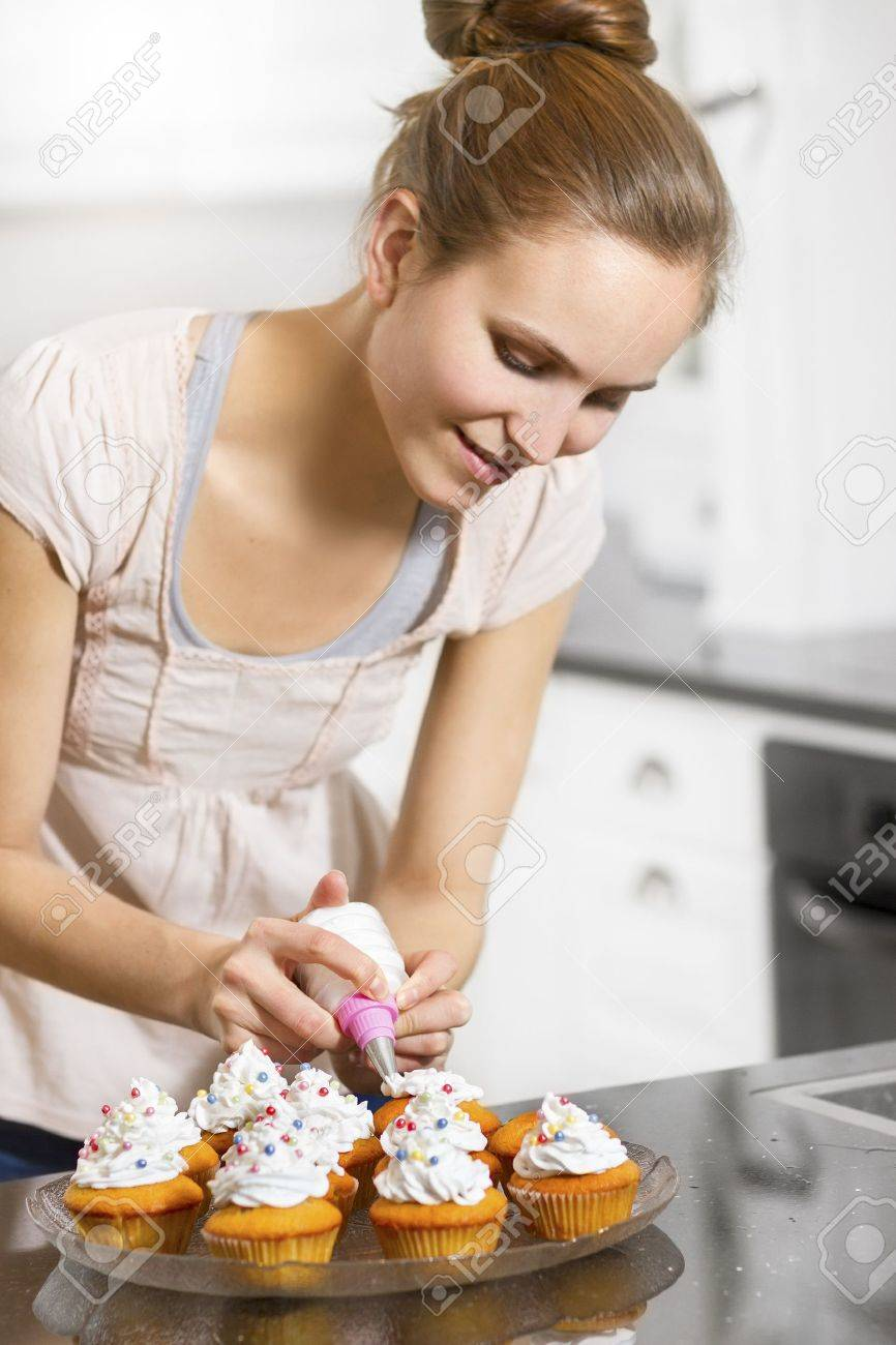 a woman baking muffins or cupcakes in white kitchen stock photo 19199826