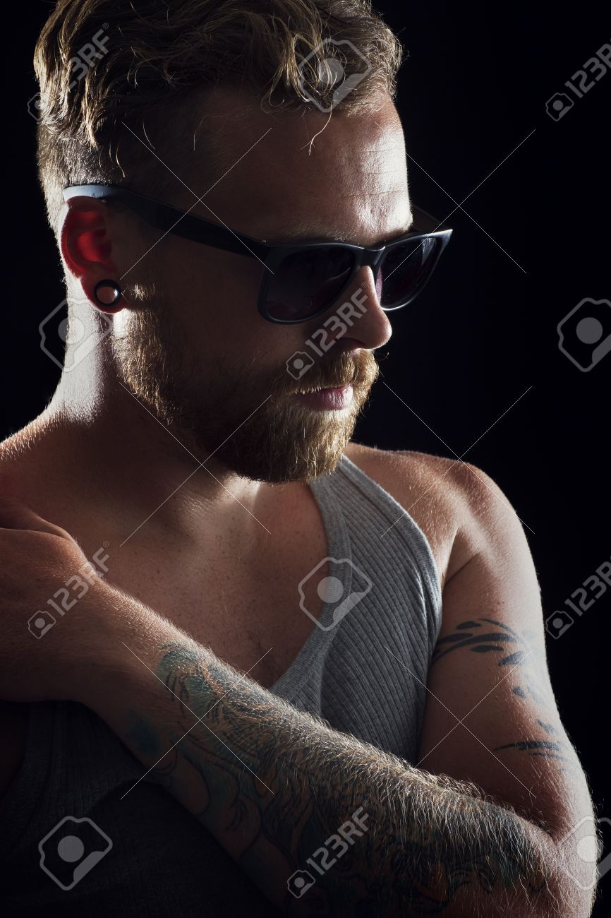 Thinking young man   rocker with ear rings, tattoo and sunglasses Stock Photo - 19200450
