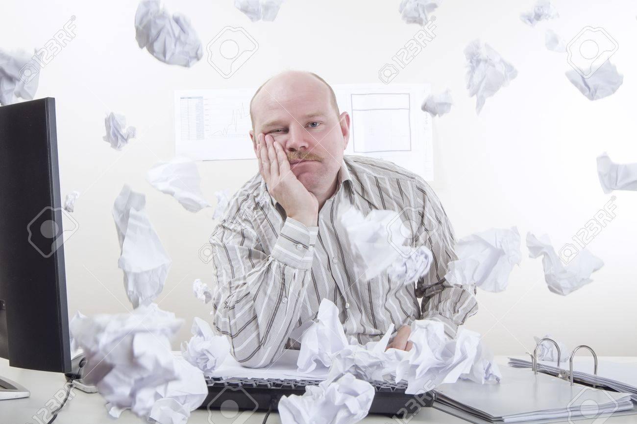 Occupé et surmené employé de bureau avec un papier volant autour