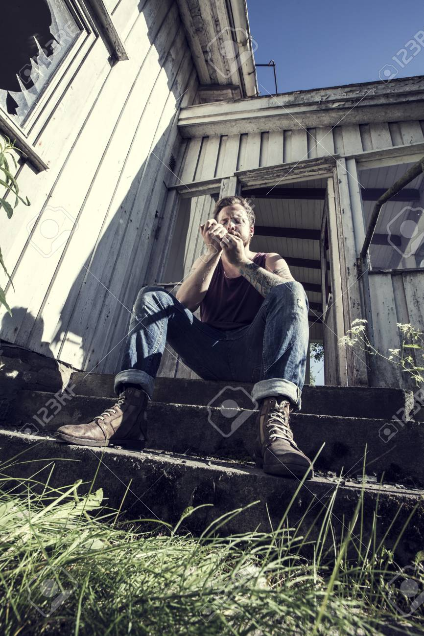 A young man sitting outside a abandoned house and lighten up a smoke Stock Photo - 20337817
