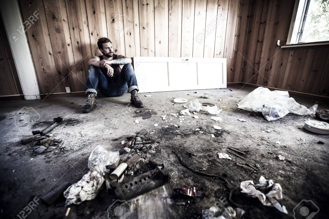 Man or redneck sits on the floor and smoke in a messy house Stock Photo - 21294673