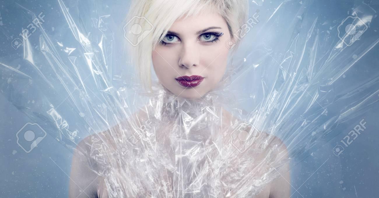 cc9f5a913 Modelo hermoso de la mujer con el plástico alrededor de su cuello y alas  tonificado, maquillaje profesional azul frío