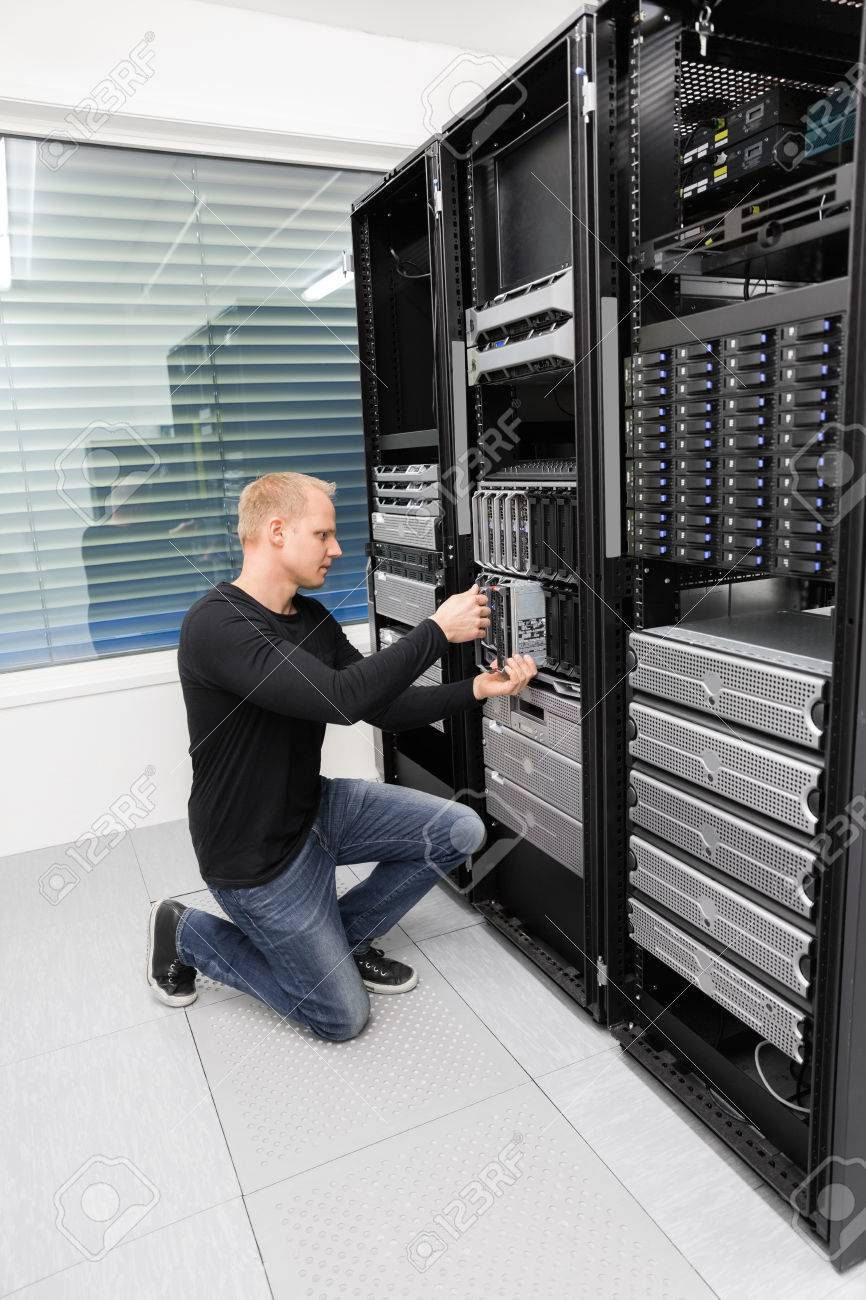 It engineer or consultant working with installation of a blade server in data rack. Shot in datacenter. Stock Photo - 27864145